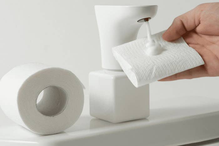 Model holding toilet paper up to Fohm dispenser