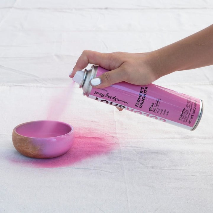 hand using pink spray paint on a dish