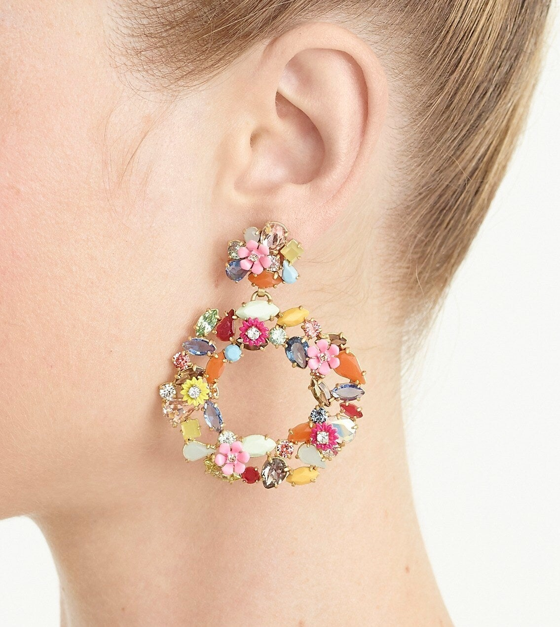 Model wearing the circular stud earrings with different colored stones and flowers
