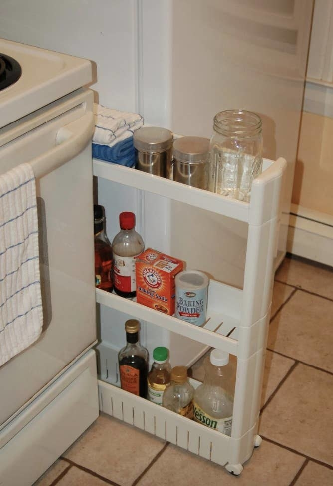Reviewer pic of the three-tier skinny tower between a fridge and stove with assorted kitchen goods on it.