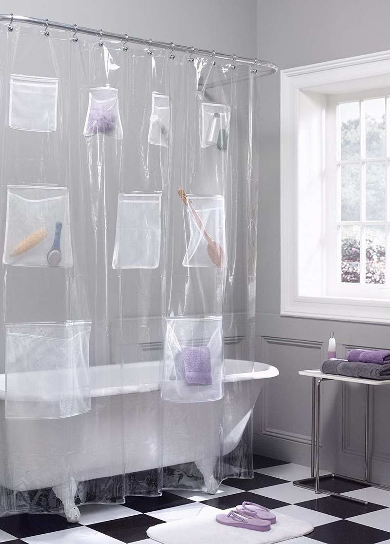 Clear shower curtain with nine pockets of different sizes all over with assorted bathroom accessories in them