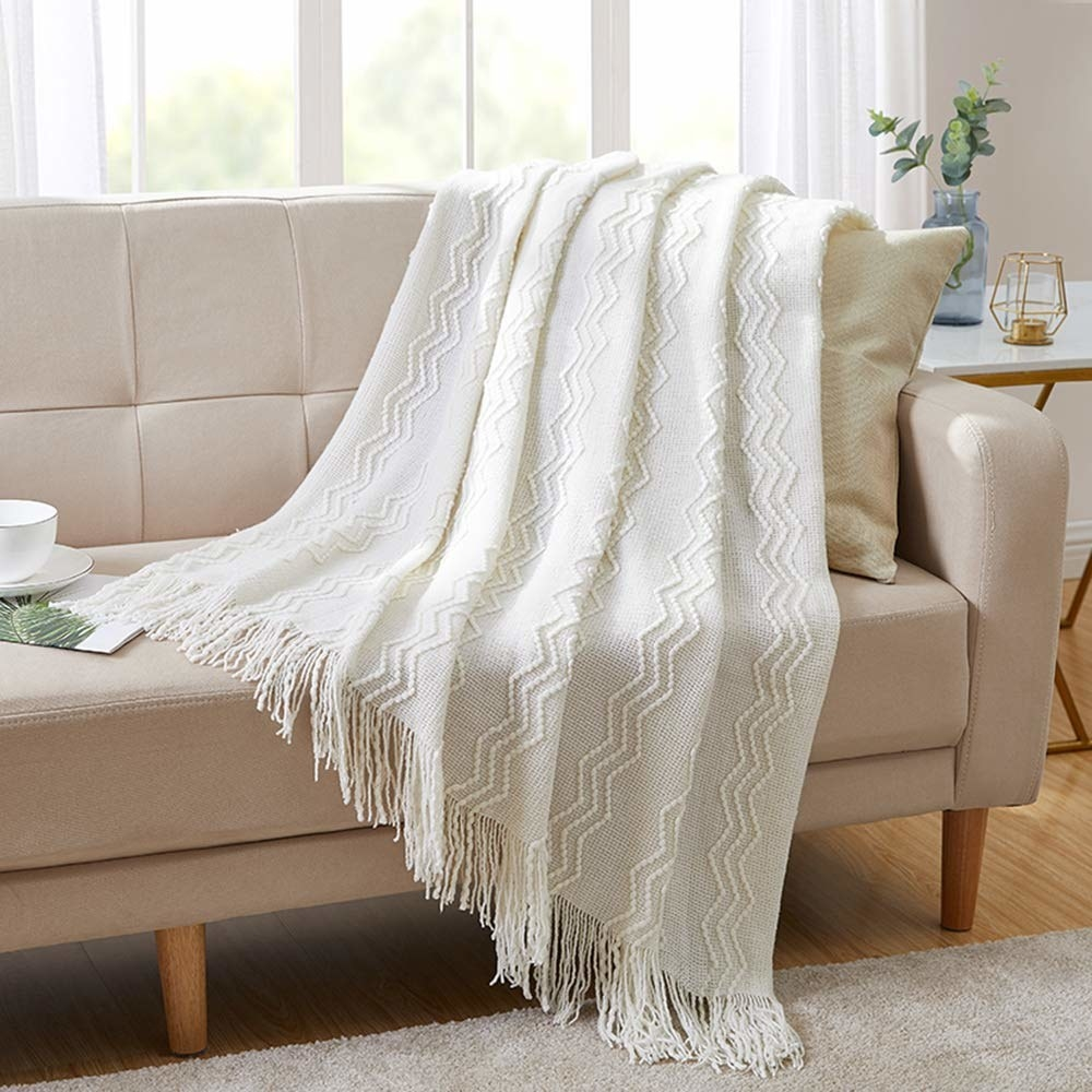 The blanket in off white thrown on a sofa