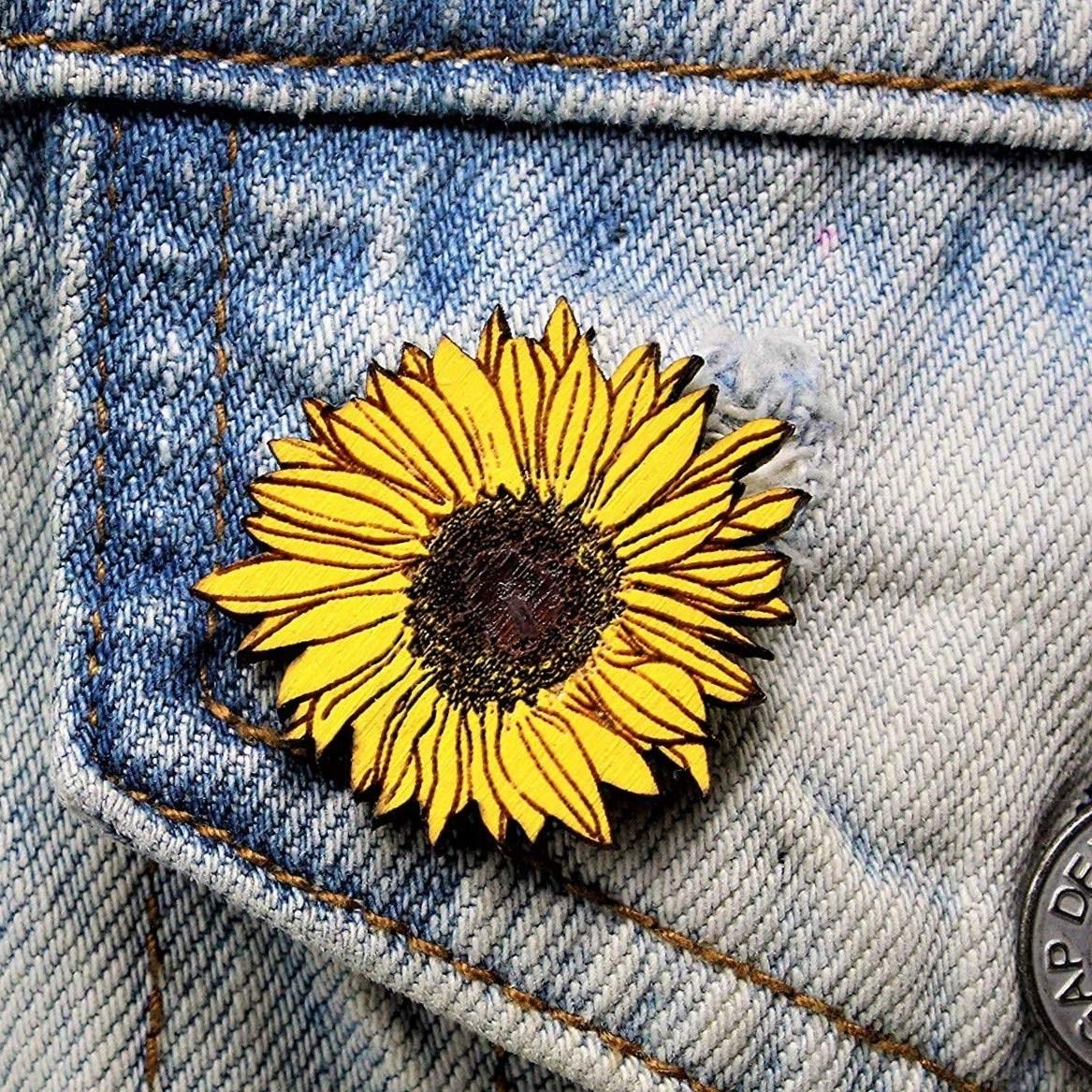 A sunflower-shaped pin on a denim jacket