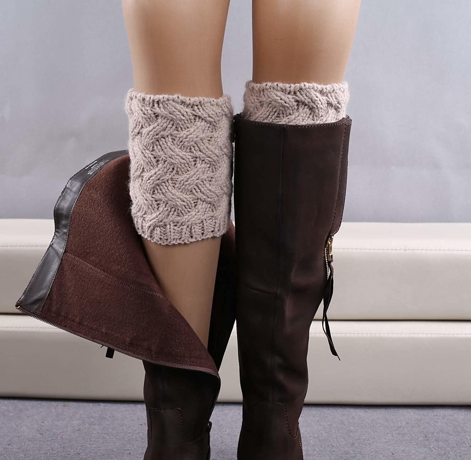 A model wearing a zipped-down boot to reveal a knit boot cuff