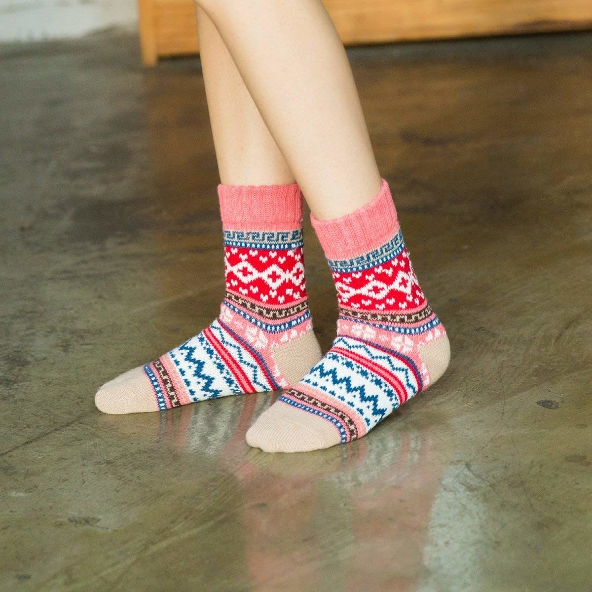 A model wearing the socks with a pink, red, brown, white, and blue Christmas sweater pattern