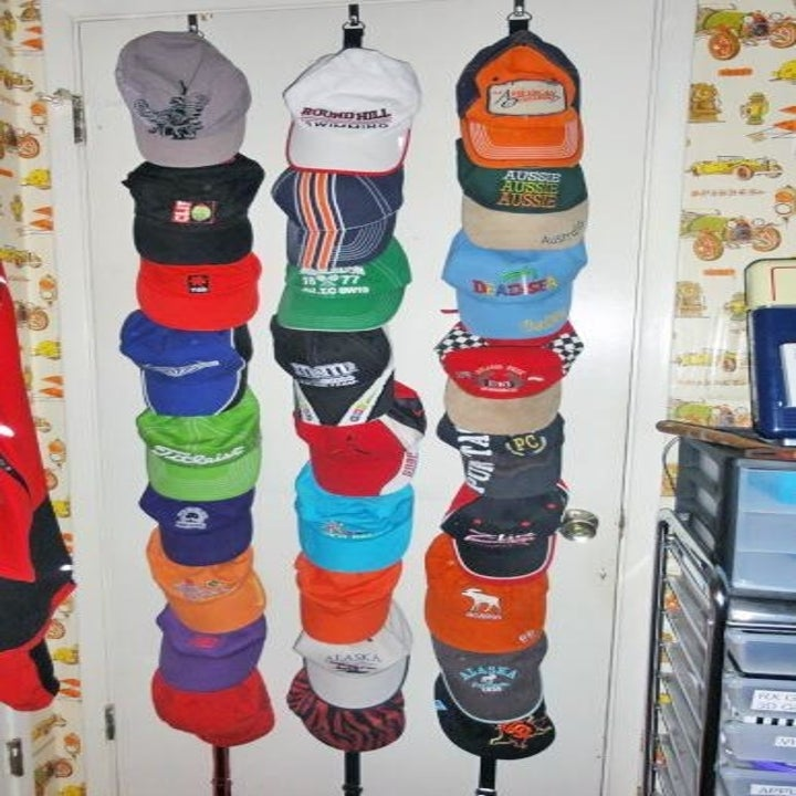 Reviewer photo of the cap holder on the back of a door holding three rows of assorted baseball caps