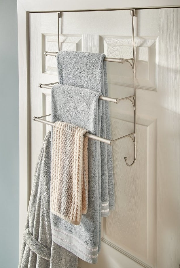 Towel rack hanging over bathroom door holding towels and robe