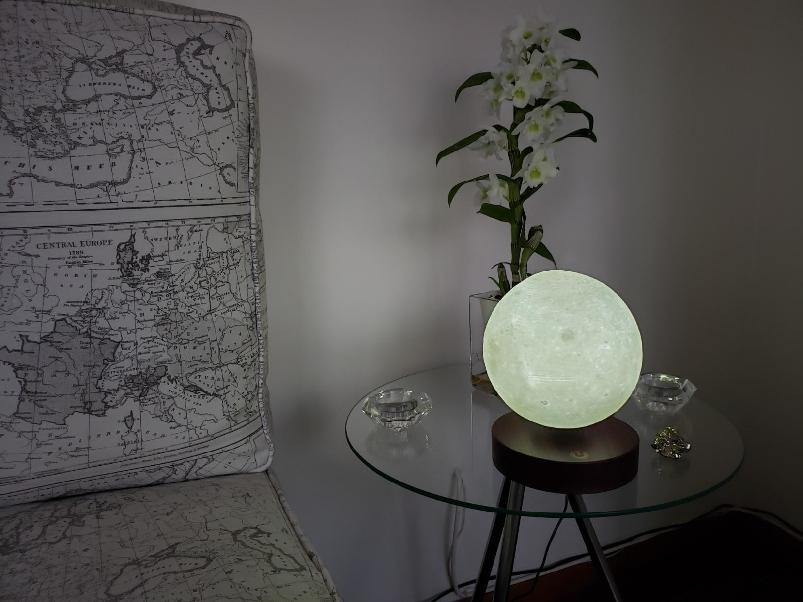 The moon lamp (complete with crater details) glowing on a side table