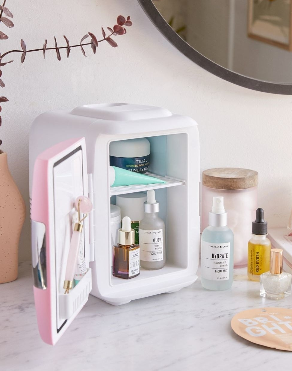 The small fridge on a counter with a pink door open, showing how it has a shelf on the inside of the door, and one in the fridge that's filled with assorted beauty products
