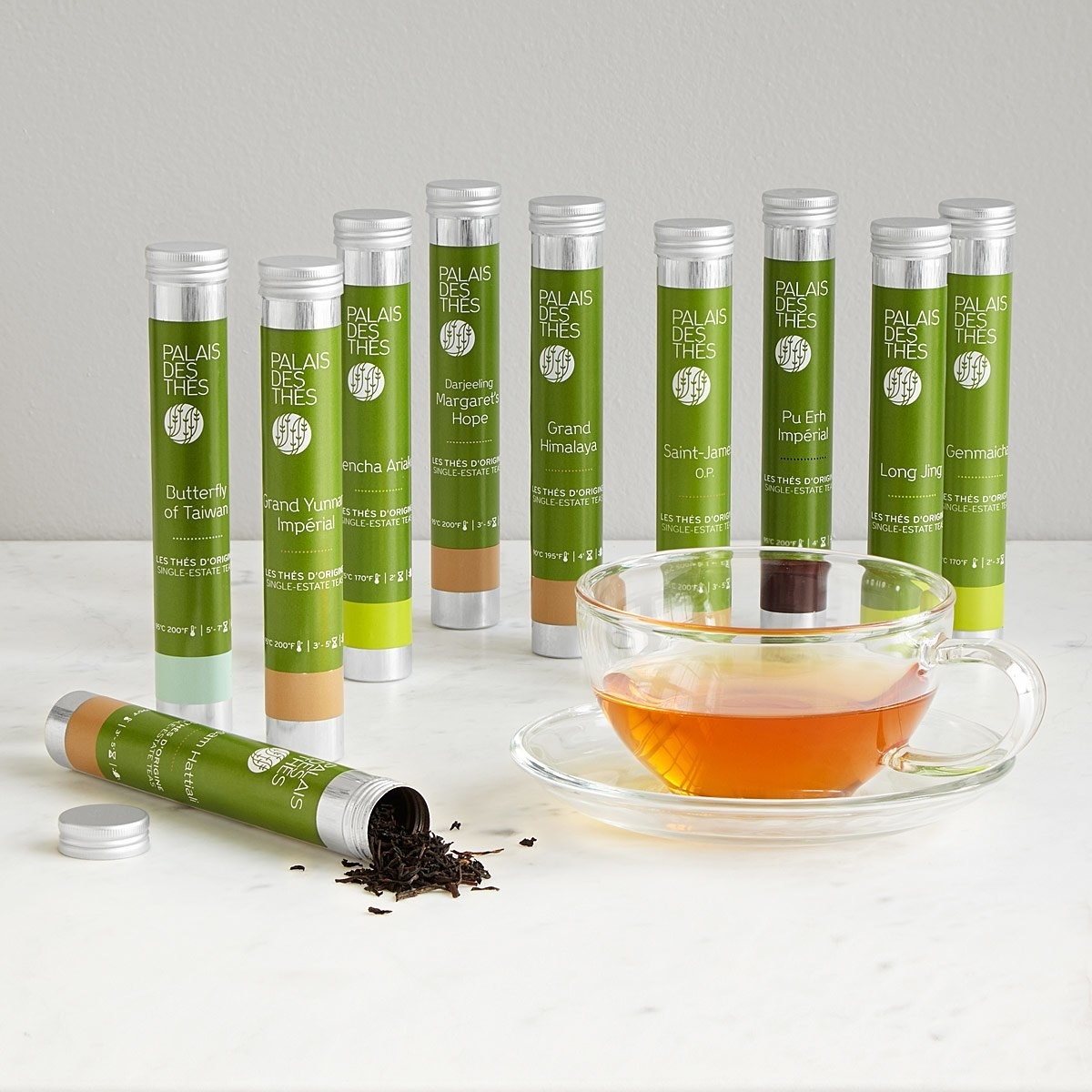 The ten thin tubes of tea with green labels saying what the kinds of tea are