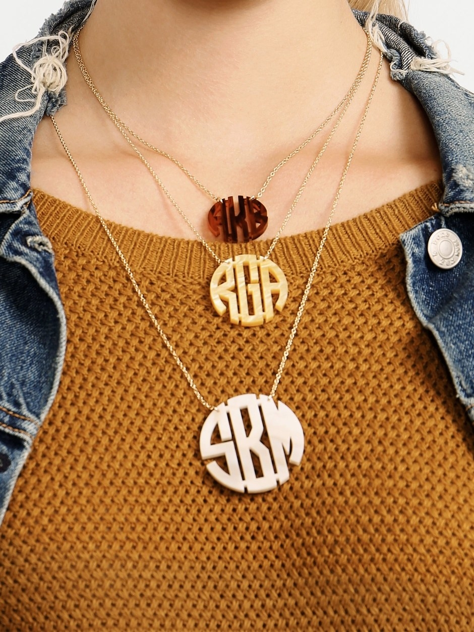 Three different sized monograms in circles in brown, beige, and white