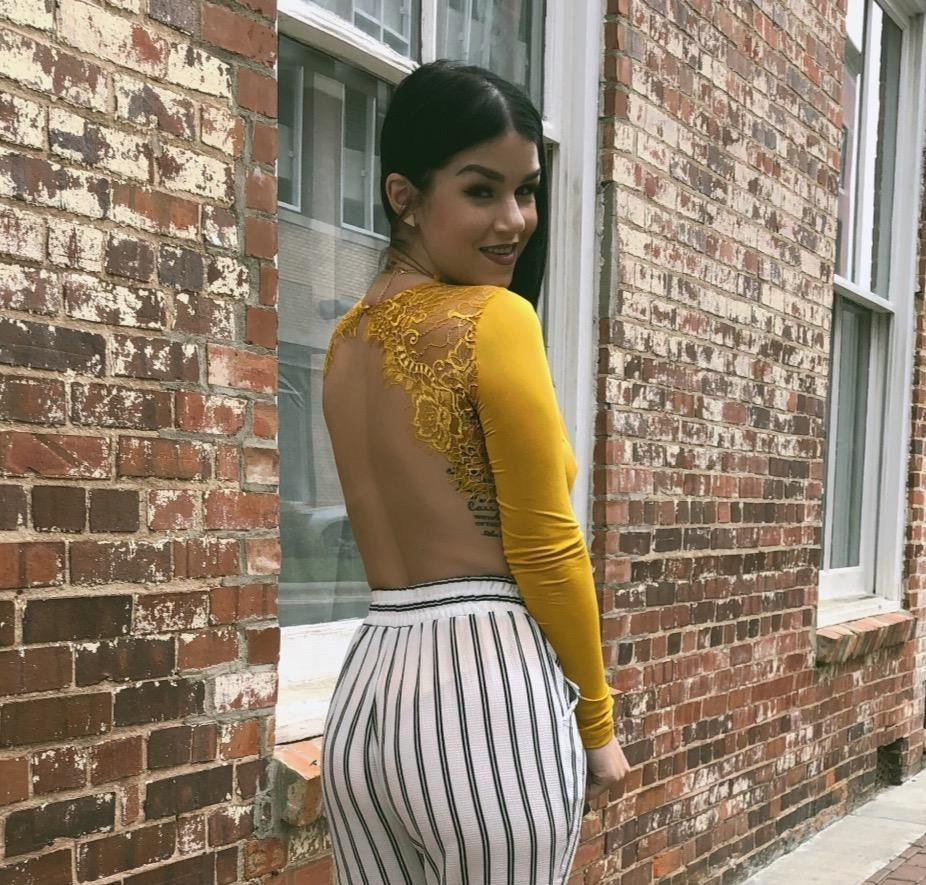 Reviewer wearing the long-sleeved bodysuit in yellow with lace on the top of the back and the rest cut out