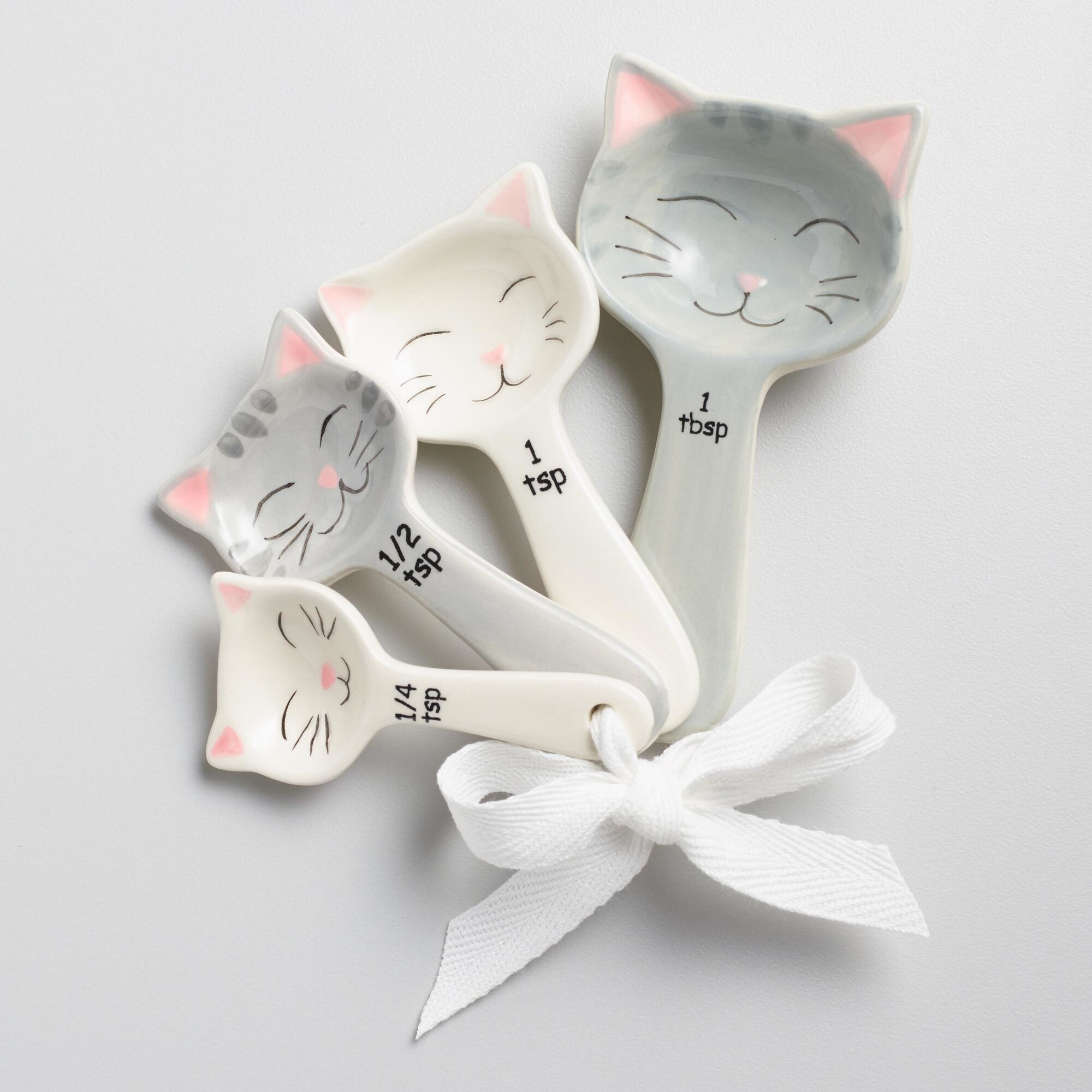 the measuring spoons with grey and white smiling cats
