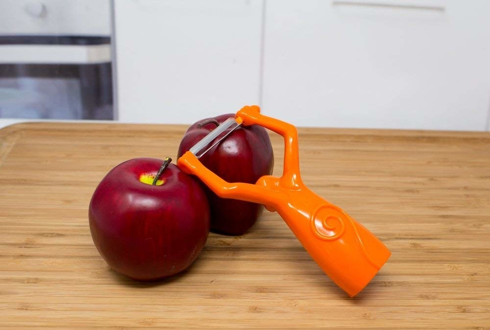 an orange monkey-shaped peeler peeling an apple