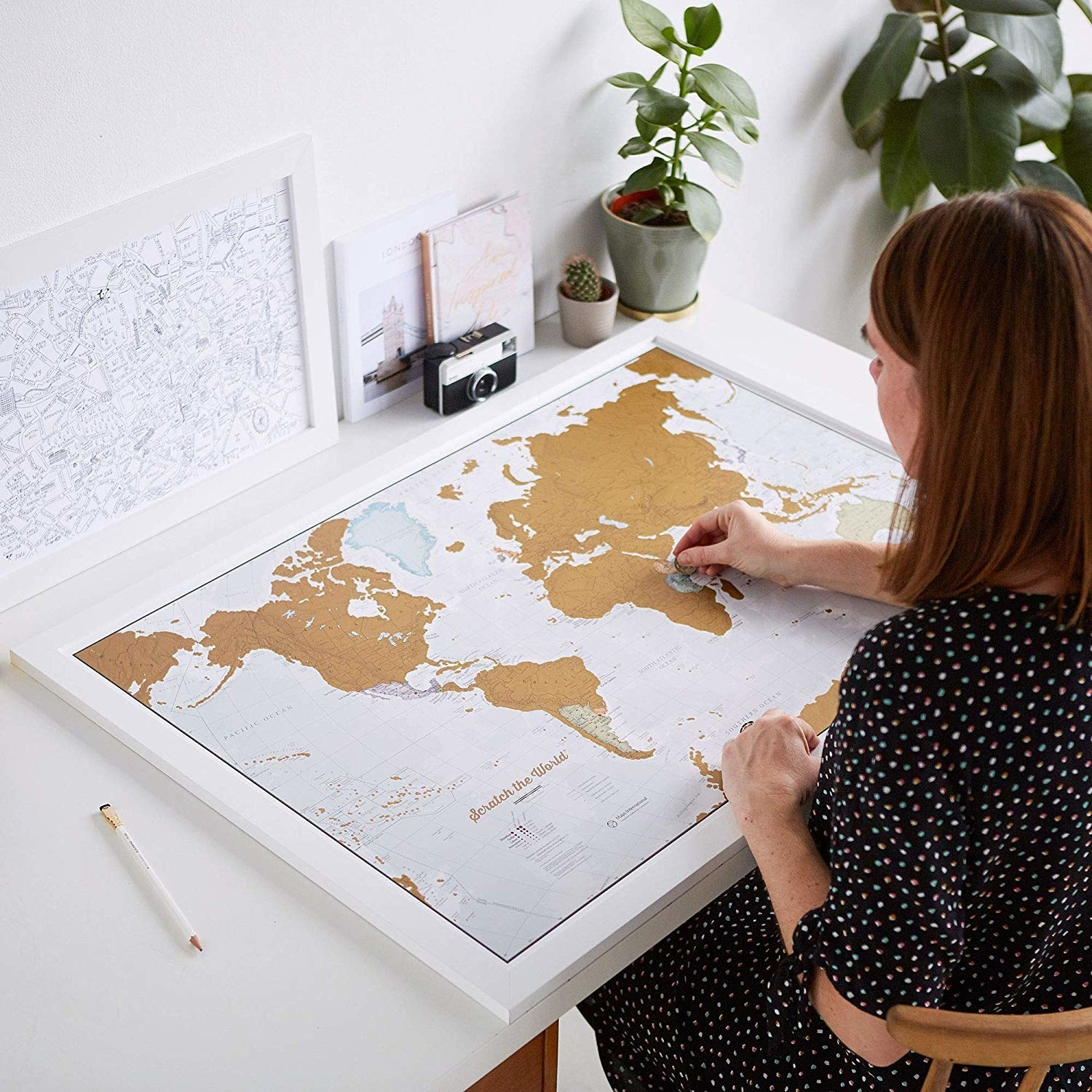 A model with the large world map on a table scratching off a country
