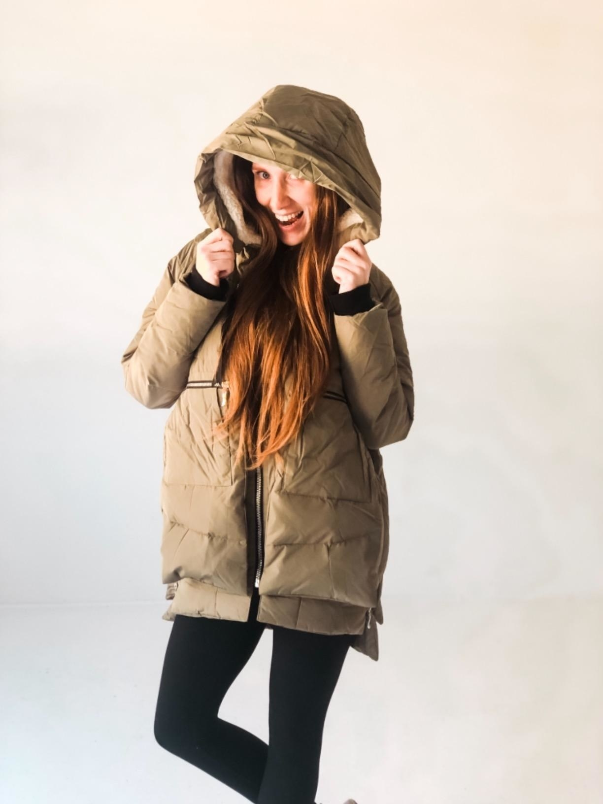 Reviewer wearing the hooded coat in olive green