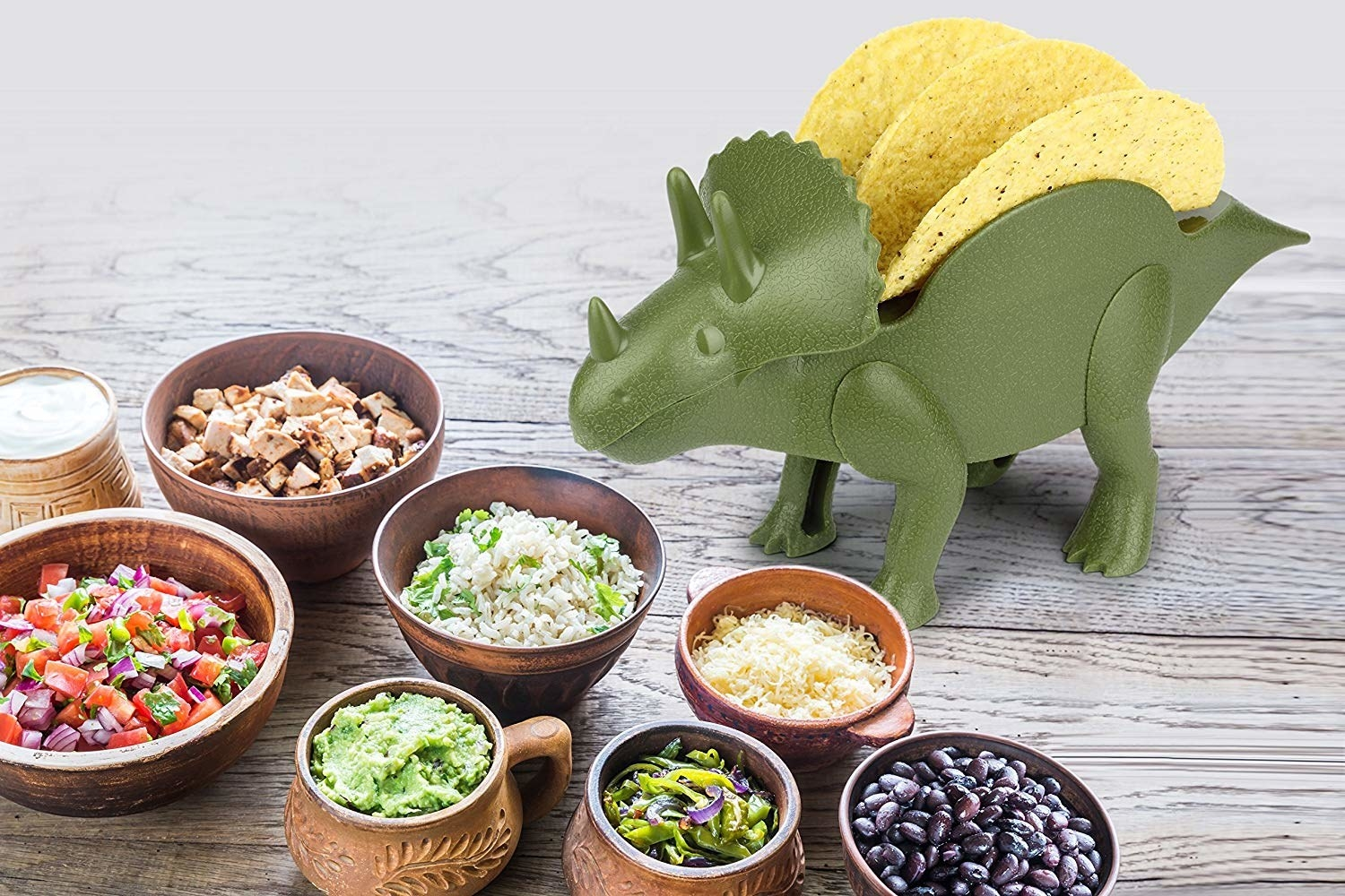 A green triceratops-shaped figure holding two taco shells on its back