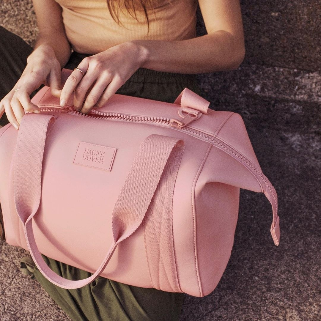 Model holding the duffle bag in pink with long zipper and shoulder straps in pink