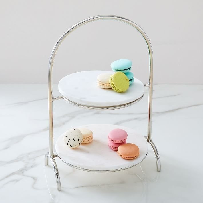 a two-tiered circle marbled dessert tray with macarons on it