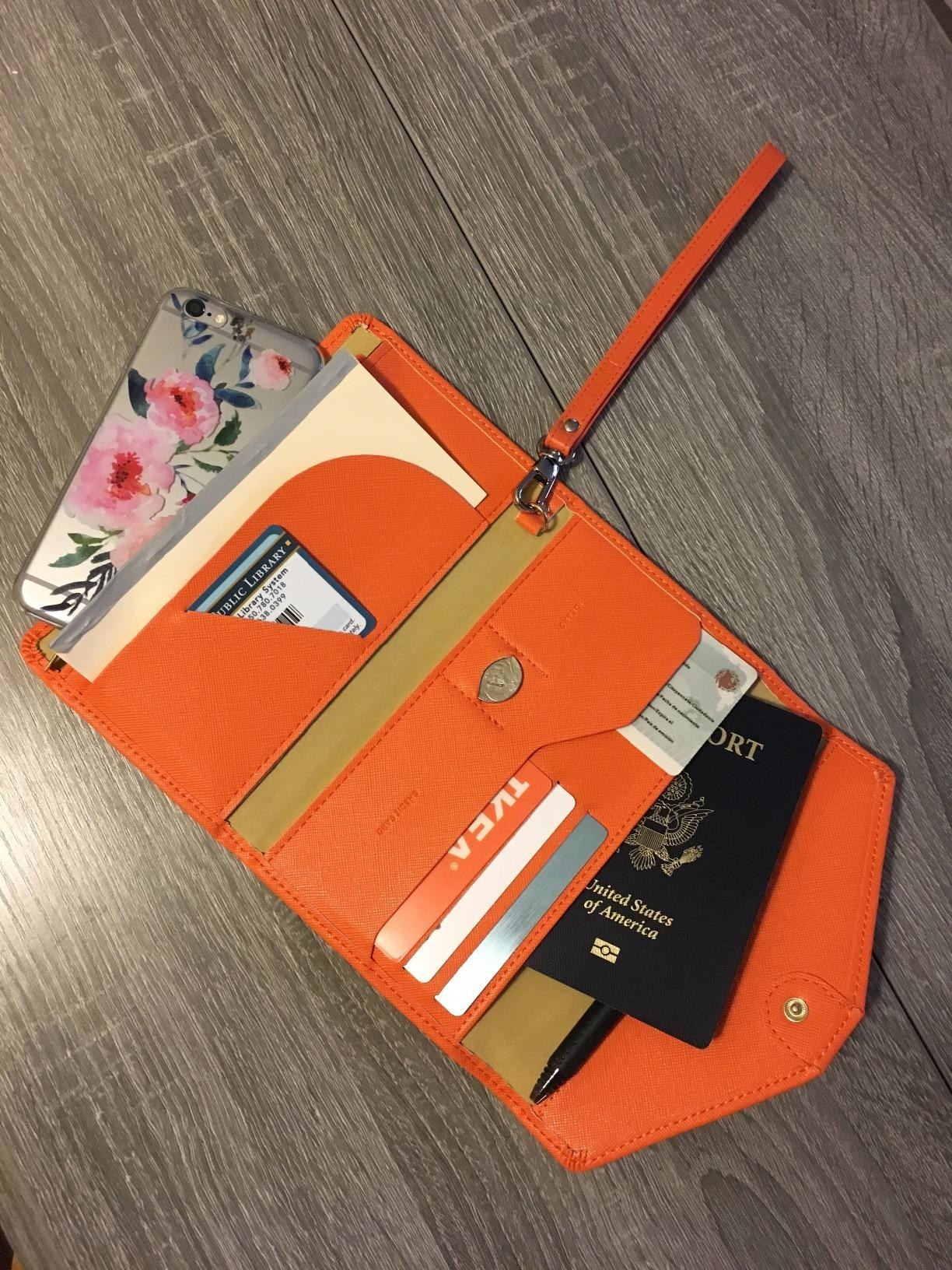 Reviewer pic of the rectangle-shaped orange wallet open, showing all the different pockets filled with cards, a passport, and other travel documents