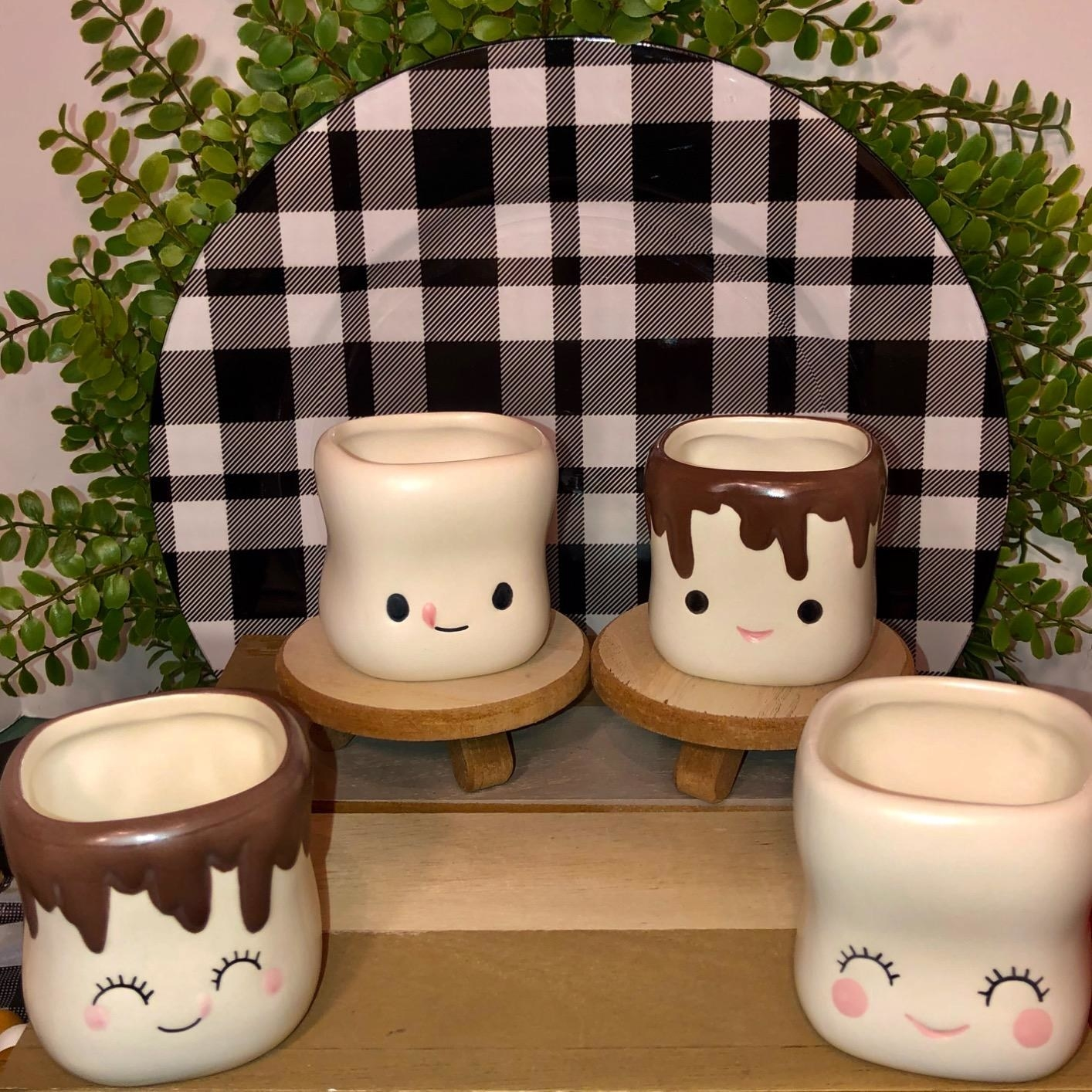 A reviewer showing four mugs designed to look like marshmallows with smiley faces on them