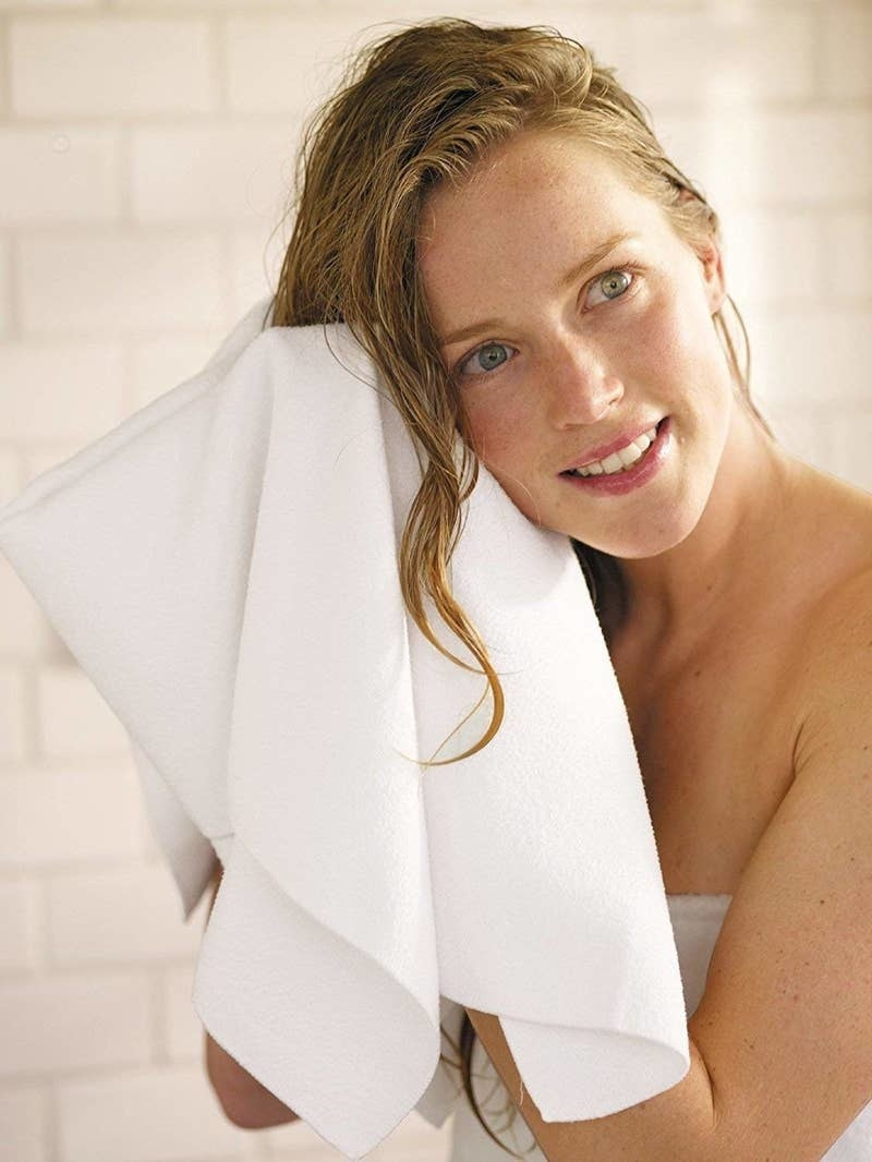 Model holding the white towel up to their wet hair