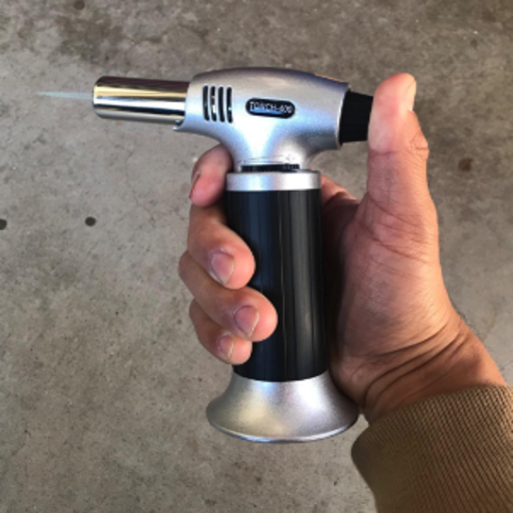 a hand holding the blow torch with a blue flame coming out of it