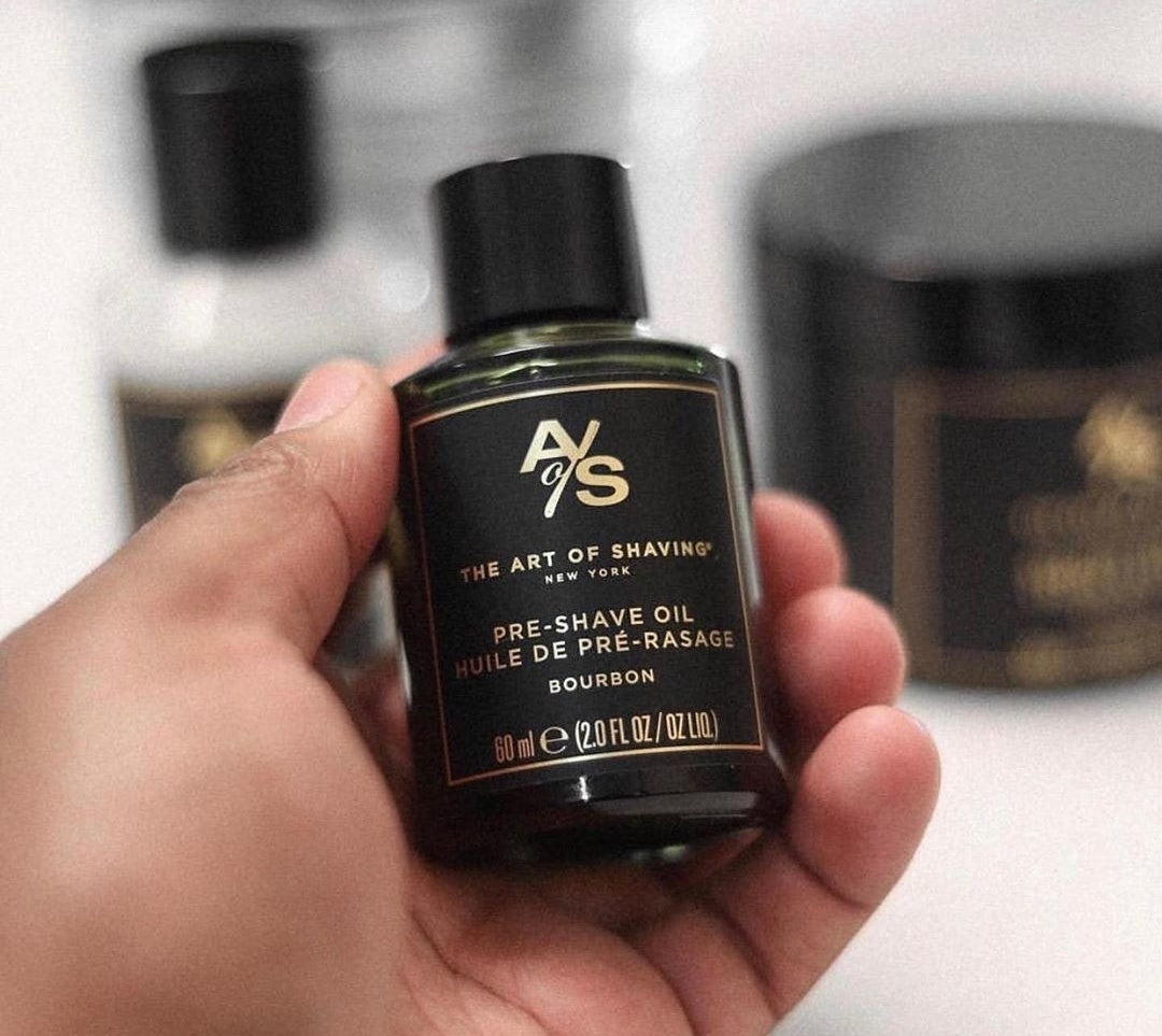 Person holding the bottle of the pre-shave oil. It has a pretty black and gold label.