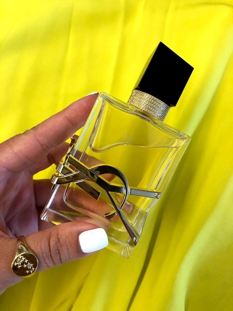 BuzzFeed Shopping member holding the full-size perfume