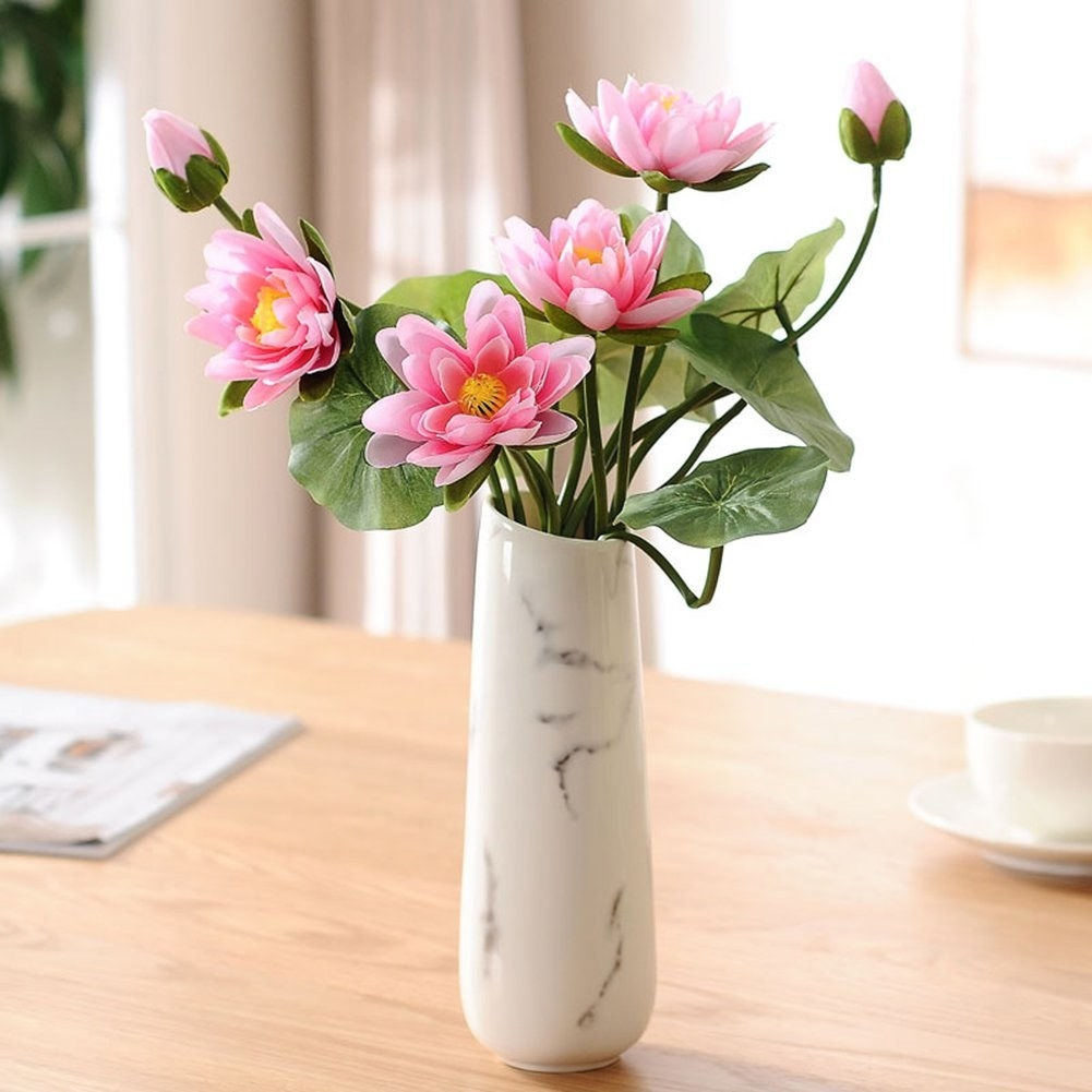 A marble-look vase filled with bright faux flowers