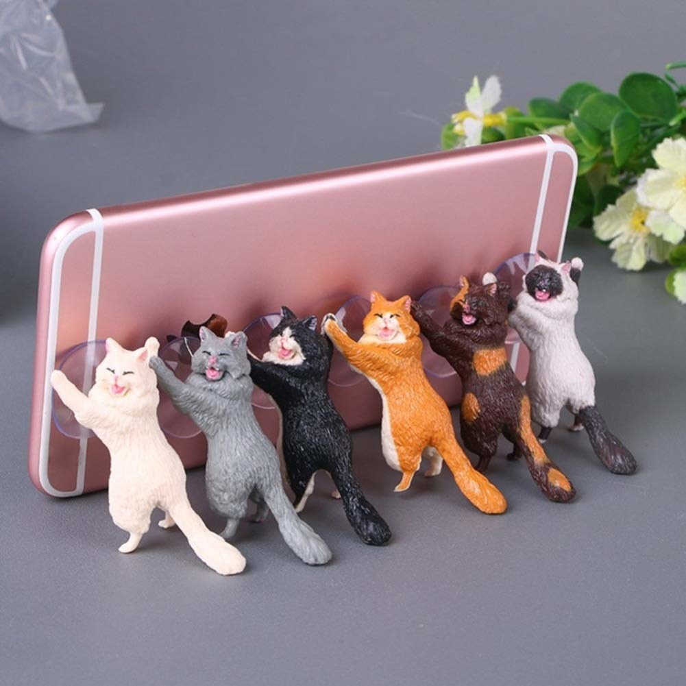 Six small cat figures in various colors with suction cups on the paws holding up a phone