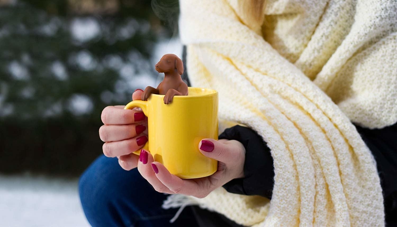 silicone dog sits on edge of mug