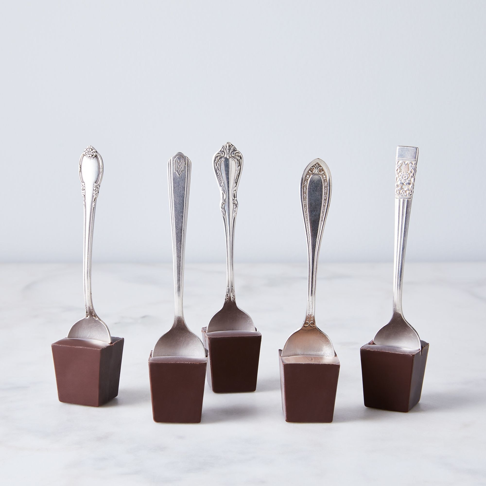 five chocolate cubes with metal spoons embedded inside