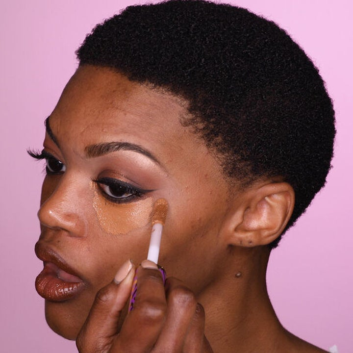 a model applying the shape tape under their eye with an applicator brush