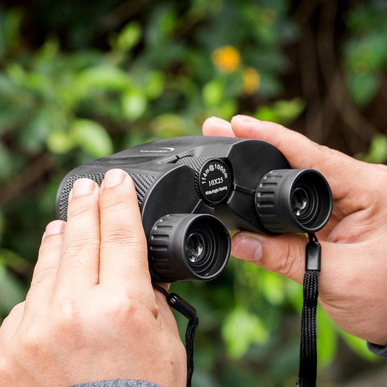 model holding small black binoculars