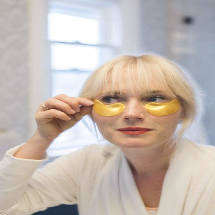 a model applying the gold under eye masks