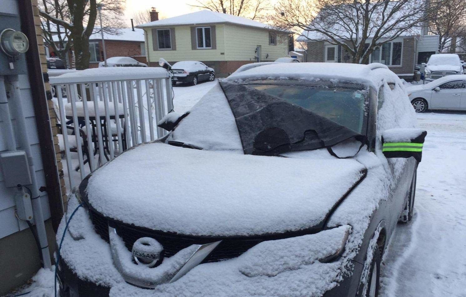 A car covered in snow with a thick tarp covering the windshield