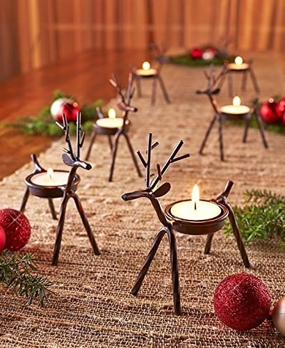 Lit up reindeer candles arranged on a table.