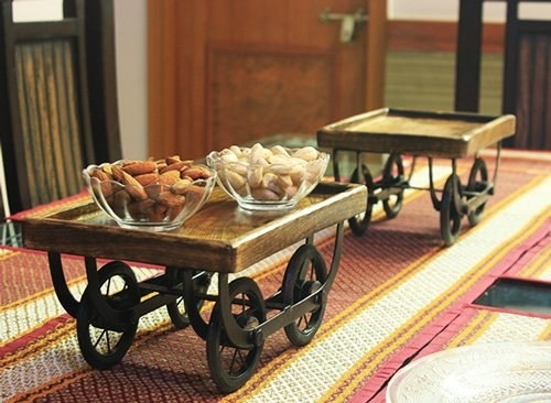 Two bowls of dry fruit placed on a wooden cart, behind another empty wooden cart, on a dining table.