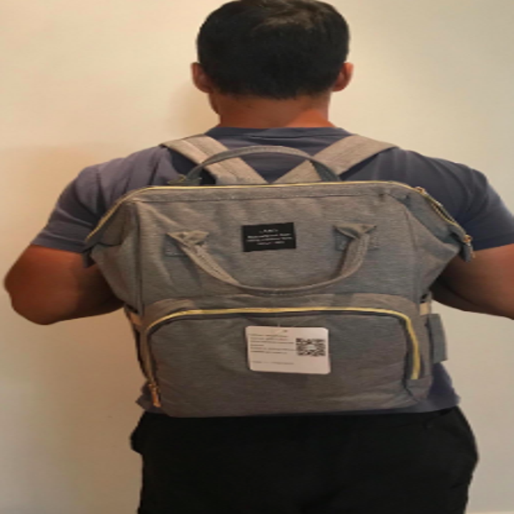 reviewer pic of person wearing the diaper bag like a backpack
