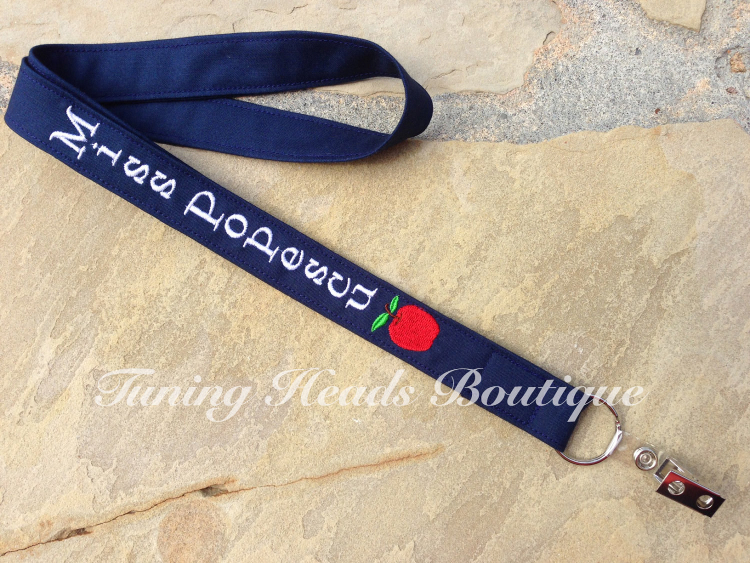 """blue fabric lanyard with """"Miss Popescu"""" embroidered in white and a red embroidered apple"""