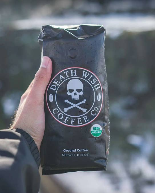 hand holding up the coffee bag with a skull and cross bones design on the bag