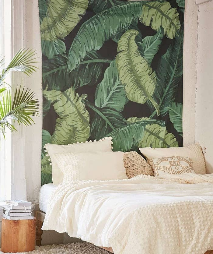 A bed in front of the banana leaf tapestry on a bedroom wall