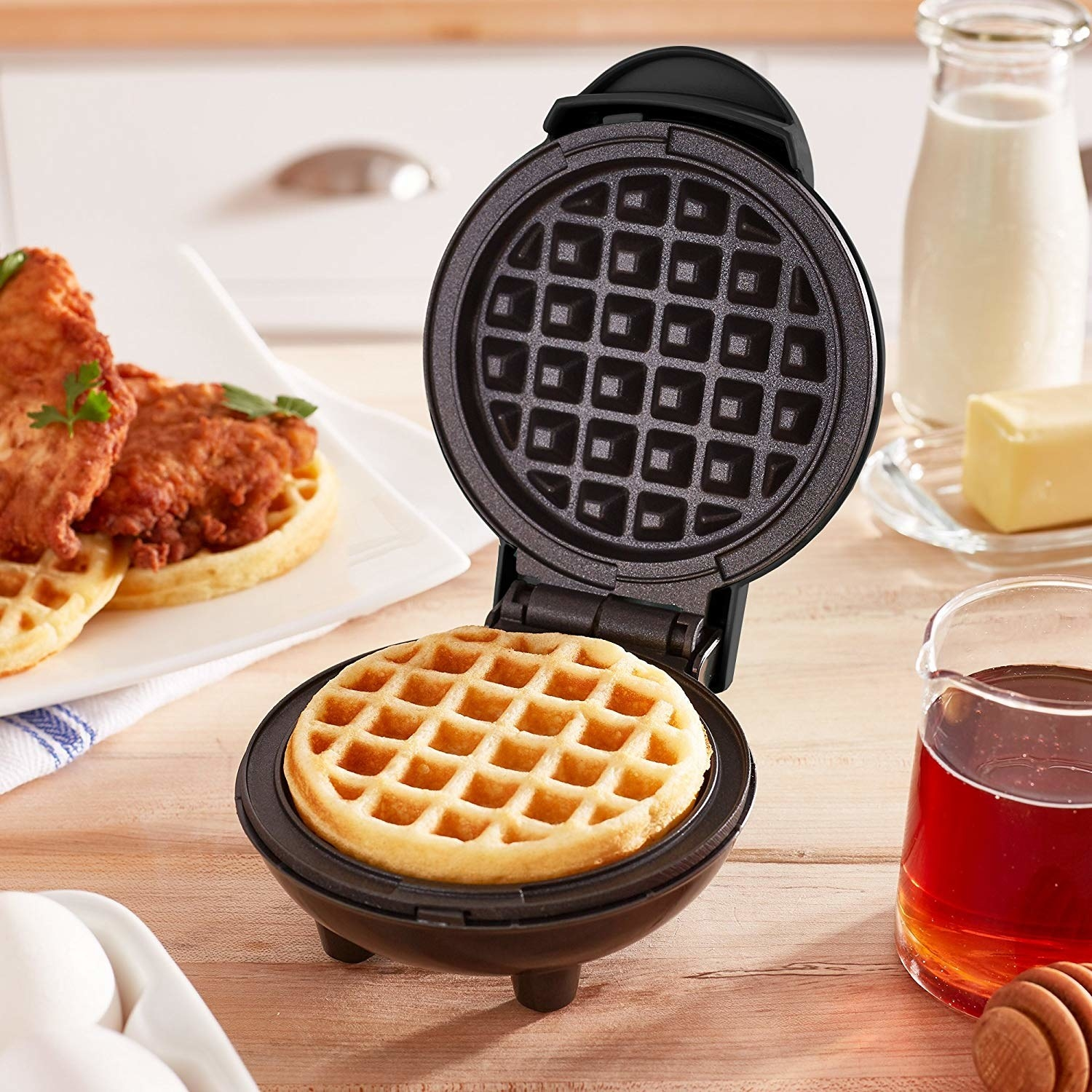 A mini waffle maker on a wooden table with a cooked waffle inside