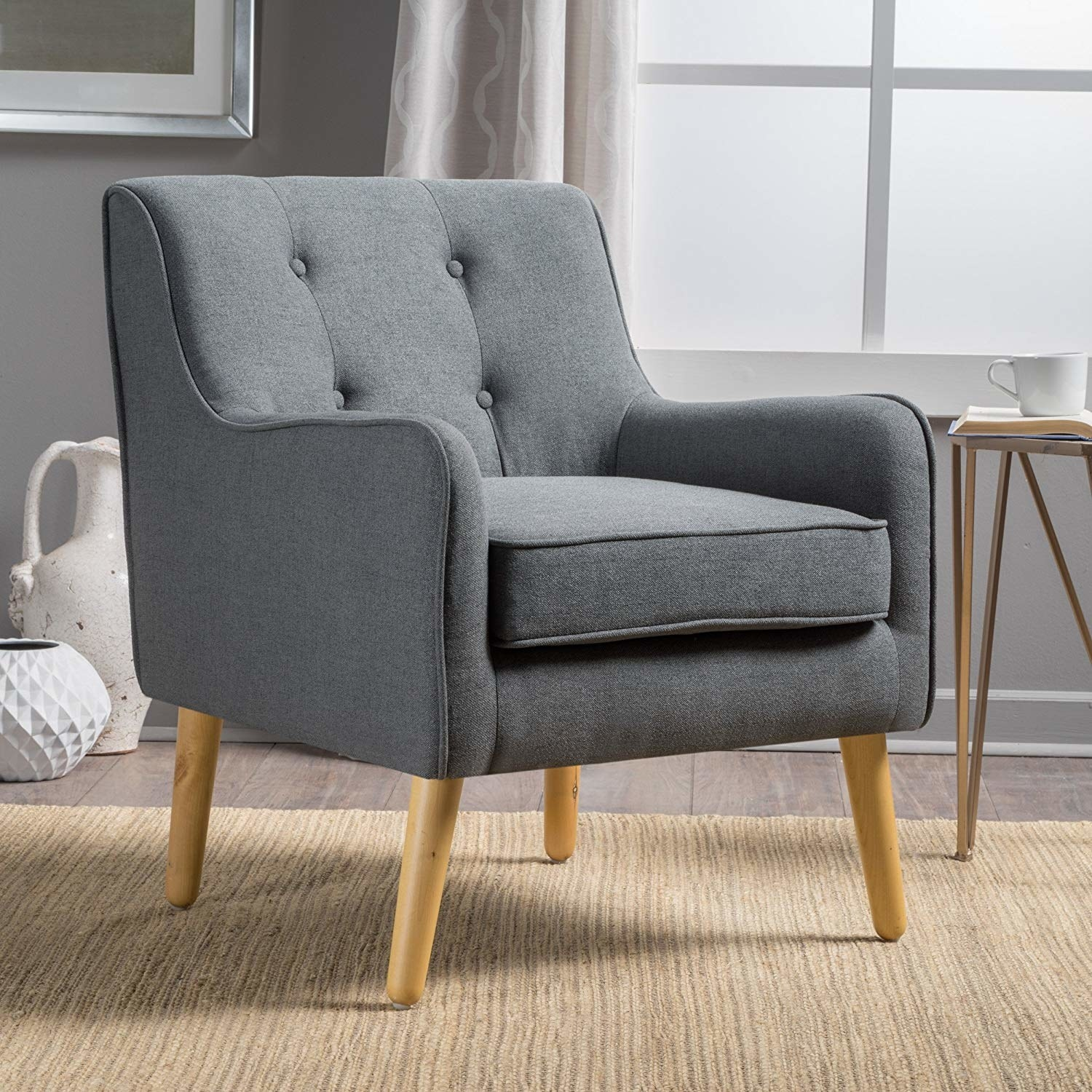 a gray arm chair with a tufted back and wooden legs