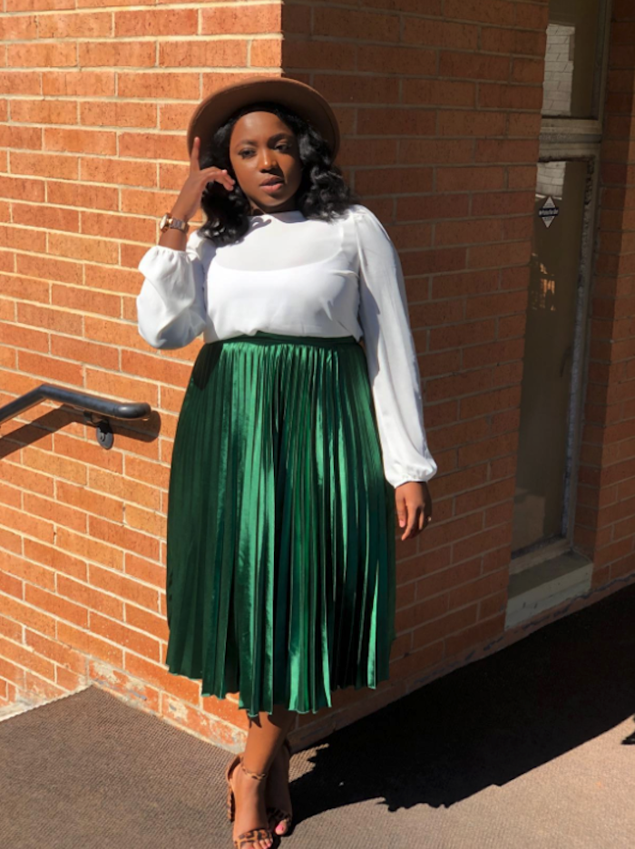 reviewer wearing the satin dark green skirt with a white long sleeve top and hat