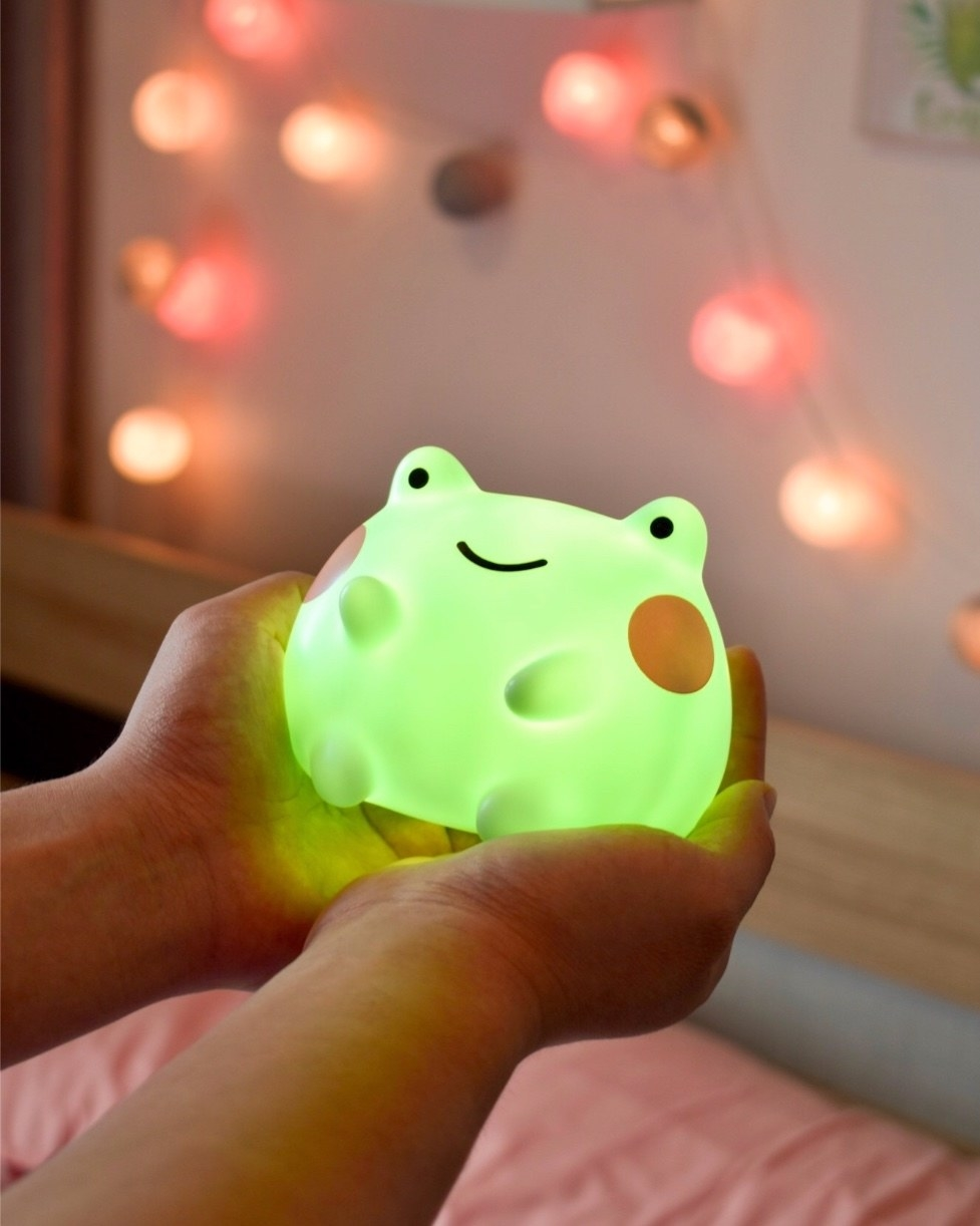 small frog light held in the palm of model's hands