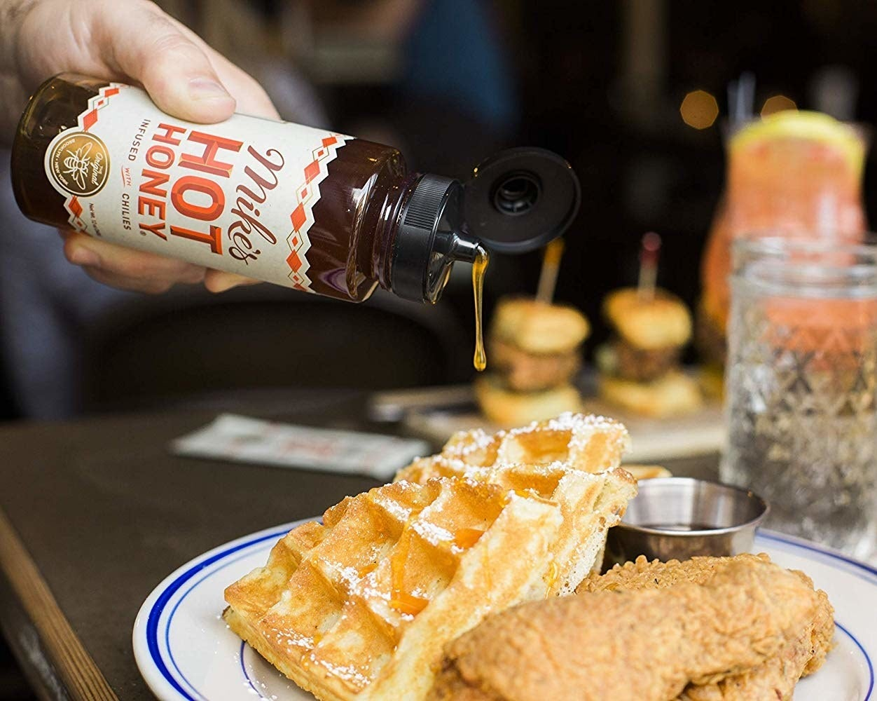 hot honey being squeezed onto chicken and waffles