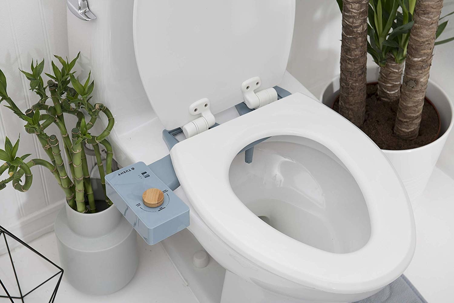 blue bidet attachment with bamboo dial on toilet