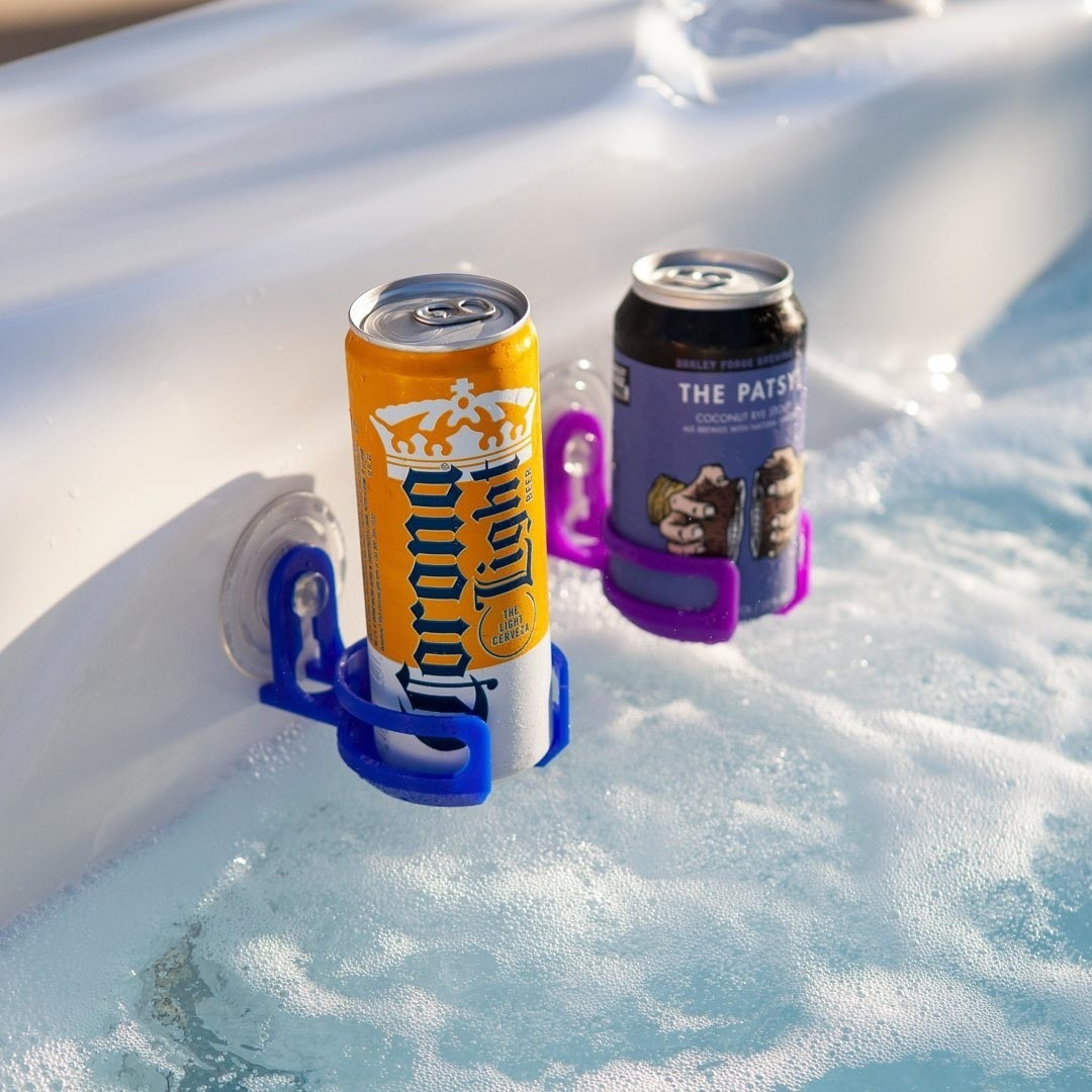 Two portable drink holders holding cans on the edge of a hot tub